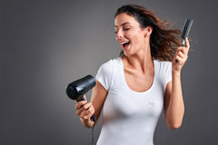 Young woman with hairdryer Royalty Free Stock Photos