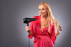 Young woman with hairdryer Royalty Free Stock Images