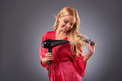 Young woman with hairdryer Royalty Free Stock Photo