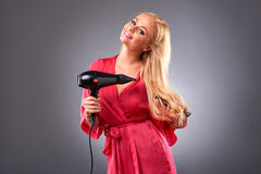 Young woman with hairdryer Royalty Free Stock Photography