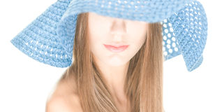 Young woman with half hidden face under blue hat. Portrait of pretty girl with her eyes under blue crocheted hat isolated on white background. Half hidden Stock Photos