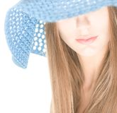 Young woman with half hidden face under blue hat. Portrait of pretty girl with her eyes under blue crocheted hat isolated on white background. Half hidden Royalty Free Stock Images