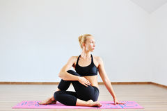Young woman in half spinal twist pose on mat.  Royalty Free Stock Images