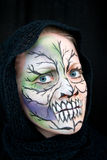 A young woman with Halloween face painting. Crazy Halloween face painting in green, blue and black on a young woman Stock Images
