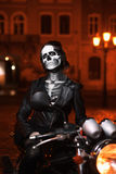 Young woman with Halloween makeup sitting on the motorbike . Street portrait. Waist up. Night city background Stock Photos