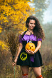 Young woman in Halloween witch costume in the autumn forest with yellow pumpkin. Stock Image