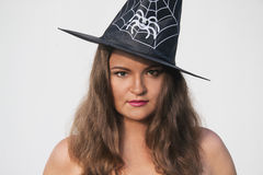 Young woman in Halloween witch hat with serious face Stock Photos