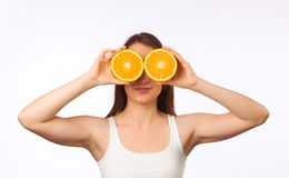 Young woman with halved orange Royalty Free Stock Images
