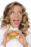 Young woman with hamburger looking away Stock Images
