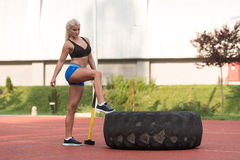 Young Woman With Hammer And Tire Resting Stock Images