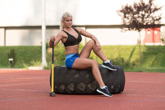 Young Woman With Hammer And Tire Resting Royalty Free Stock Images