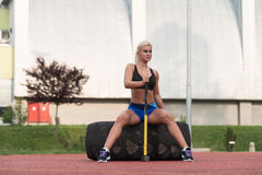 Young Woman With Hammer And Tire Resting Royalty Free Stock Photo