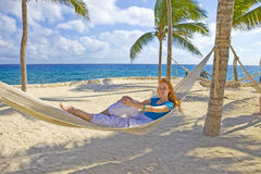 Young woman in hammock on background of palm trees Stock Images