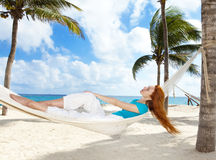 Young woman in hammock on background of palm trees Royalty Free Stock Photography