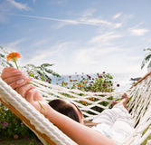 Young woman in hammock, focus on the flower Royalty Free Stock Image