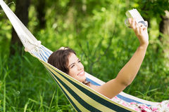 Young woman in a hammock in garden doing snapshot. Stock Photography