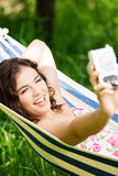 Young woman in a hammock in garden doing snapshot. Young woman lying in a hammock in garden doing snapshot Stock Photography