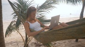 Woman freelancer works on the beach in hammock. Young woman in hammock with a laptop overlooking the sea. Woman freelancer works on the beach stock video footage