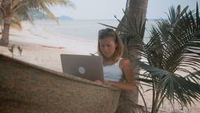 Woman freelancer works on the beach in hammock. Young woman in hammock with a laptop overlooking the sea. Woman freelancer works on the beach stock video
