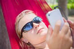 Young woman in hammock under palm trees on ocean beach listen mu Stock Photography