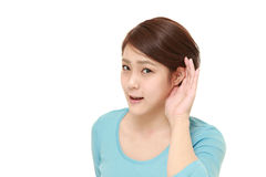 Young woman with hand behind ear listening closely  Stock Image