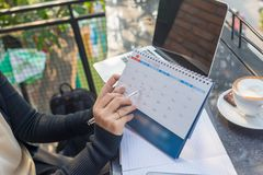 Young woman hand carrying calendar and pointing on it by pen stock images
