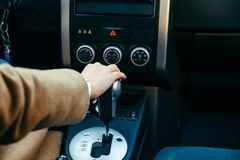 Young woman hand on gear shift stick in car. Road trip stock photo