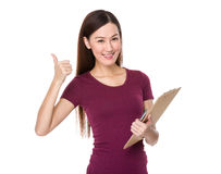 Young woman hand hold with clipboard and thumb up Stock Photo
