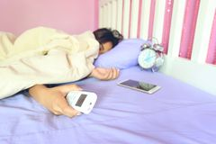 Young woman hand hold remote air conditioner and sleeping in the royalty free stock photography