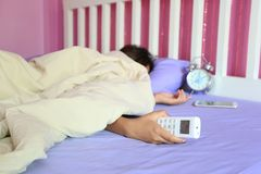 Young woman hand hold remote air conditioner and sleeping in the stock photography