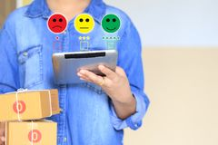 Young woman hand holding smartphone and putting check mark with smiley face marker and green marker on five stars of delivery stock image