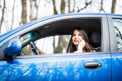 Young woman with hand on steering wheel using mobile phone while driving on road. Young woman with hand on steering wheel using mobile phone while driving Royalty Free Stock Photo