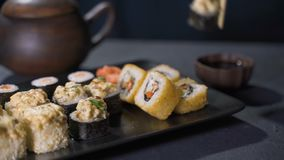 Hand with sticks takes sushi. Concept of Chinese sticks sushi rolls on a dark plate.