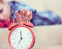 Young woman hand switches off the alarm clock in the morning close up. royalty free stock photos