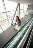 Young woman with handbag walking at modern airport terminal Stock Images