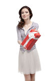 Young woman hands a birthday gift. Wrapped in red paper, isolated on white Stock Photography