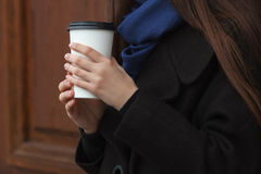 Young woman hands with coffee disposable cup outdoors with wooden doors background Stock Image