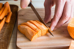 Young woman hands cutting slicing sweet potatoes into wedges preparing dinner Stock Photo