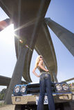 Young woman with hands on hips by car beneath overpass, low angle view (sun flare) Stock Photography