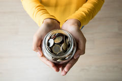 Young woman hands holding glass jar with multi currency coins inside Stock Photography