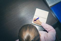 Young woman hands holding open notebook pages on a dark table, top view. list. the doctor writes a note, a shopping list. the plan. Young woman hands holding stock photos