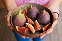 Young woman hands holding pot. Hands holding a copper pot with figs Royalty Free Stock Image