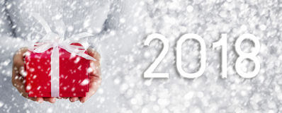 Young woman hands holding red gift box with snow on silver bokeh. Background Royalty Free Stock Photo