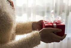 Young woman hands holding red gift box with white ribbon. For christmas and new year and other celebration Royalty Free Stock Photography
