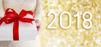 Young woman hands holding white gift box on gold bokeh with 2018 Royalty Free Stock Images