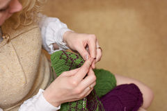 Young woman hands knitting with two coloured wool. Hands of a young woman knitting with two coloured wool stock photo