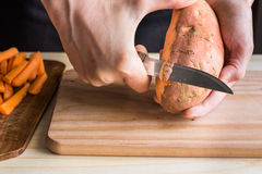 Young woman hands peeling with knife sweet potato, over wooden cutting board, preparing dinner Royalty Free Stock Image