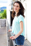 Young woman with hands on railing smiling Stock Photo