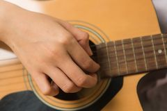 Young woman hands touching guitar chords. Young Asian woman hands touching guitar chords stock photos
