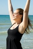 Young woman with hands up expressing joy on the coast. In sunshine royalty free stock images